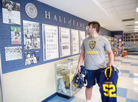 Our Lady of Lourdes football player Jake Timm glances over his shoulder at the school's hall of fame before beginning his workout on August 7, 2019.