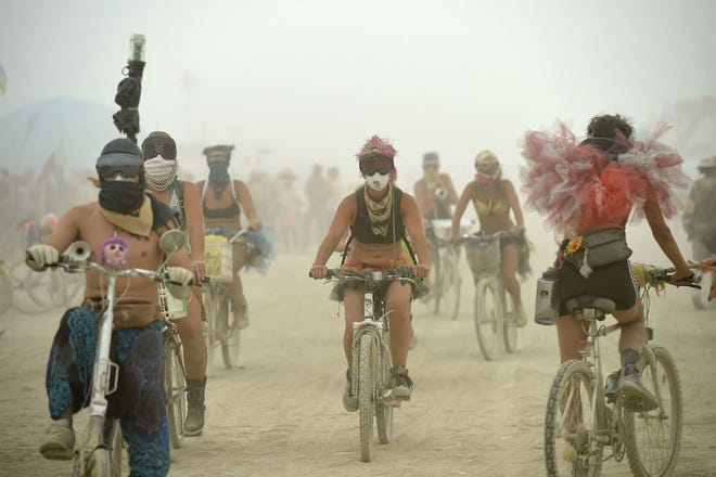Burners ride through the streets of Black Rock City during a dust storm at Burning Man on Aug. 28, 2017.