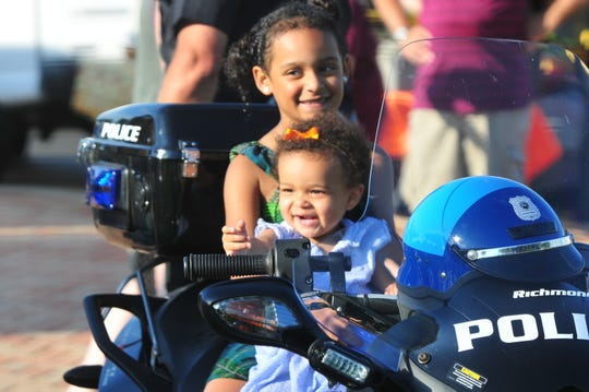 Caliah Coronado (back), 7, and 18-month-old Ryah Coronado sit on a Richmond Police Department motorcycle Tuesday, Aug. 6, 2019, at Elstro Plaza.