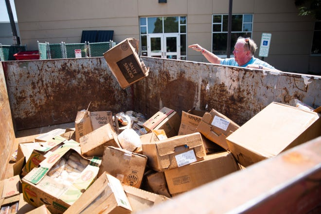 Daryl Meyer from The Banquet throws food in the dumpster after a sprinkler system damaged all the food inside the freezer, Wednesday, Aug. 7.