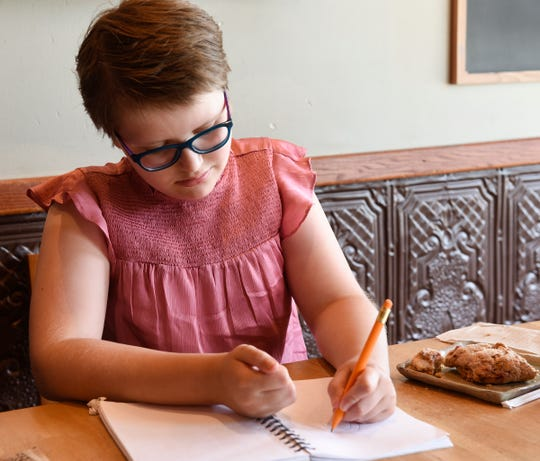 Eliana Szabo draws in her notebook Tuesday, Aug. 6, 2019, at The Local Blend in St. Joseph.