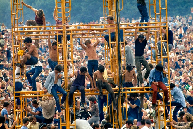 Bethel, New York: August 1969. Crowd and people sitting on the sound tower at Woodstock.  ©Elliott Landy / The Image Works.