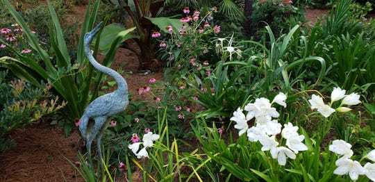 The bird statue acts as a center piece to the garden bed.