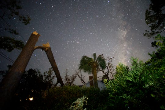 The Milky Way shines over a broken tree and scattered limbs on Oct.11 in Panama City. Hurricane Michael knocked down power lines in most of Panama City Fla. during the storm. This eliminated normal amounts of light pollution in the area and allowed the night sky to shine over Bay County.   [Patti Blake/The News Herald]