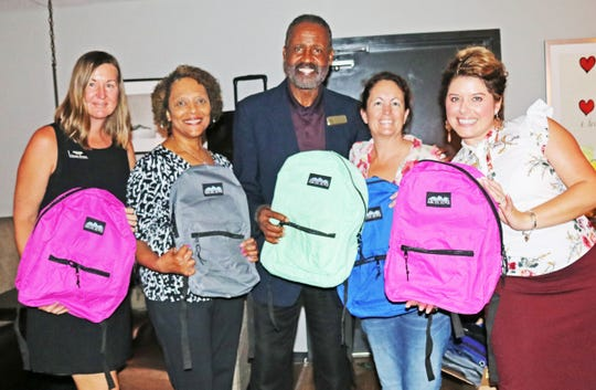 Gifford Youth Achievement Center's Angelia Perry, second from left, and Freddie Woolfork collect backpacks at the Vero Premier Women's Network Mixer from Susan Lorenz, left, Kitty Wagner and Anna Valencia-Tillery.