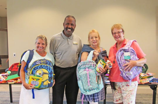 Gifford Youth Achievement Center's Freddie Woolfork, second from left, accepts backpacks and school supplies from Stacy Spangler, left, Christine Preston and Nancy Hartsock from The Lakes at Waterway Village.