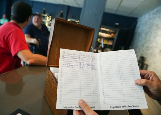 Co-owner Denise Terrance-Campion holds a customer's brew traveler passport at Edgewood Eatery on Tuesday, Aug. 6, 2019, in Vero Beach. The restaurant is currently promoting their extensive list of local craft beers by offering a brew traveler passport.