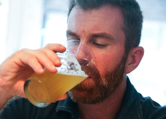 Michael Forbes, of Vero Beach, drinks an India Pale Ale by Fort Pierce-based Sailfish Brewing Company, at Edgewood Eatery on Tuesday, Aug. 6, 2019, in Vero Beach. The restaurant is currently promoting their extensive list of local craft beers by offering a brew traveler passport.