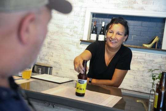 "Co-owner Denise Terrance-Campion hands a La Rubia, an American Blonde Ale, brewed by Miami-based Wynwood Brewing Company to customer Derek Thompson at Edgewood Eatery on Tuesday, Aug. 6, 2019, in Vero Beach. The restaurant is currently promoting their extensive list of local craft beers by offering a brew traveler passport. At 25 beers the customer gets a t-shirt, and at 50 beers they earn $1 off each beer for a year as well as a $25 gift certificate. ""There's about 320 micro breweries right now inside of Florida and there's going to be more in the near future,"" said Terrance-Campion. ""It's a big state, so why we would put everybody on the road when we could bring the best of what Florida has to offer as far beers right here."""