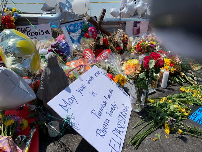Mourners leave signs at a makeshift memorial near a Walmart in El Paso where 22 were killed and dozens more injured.