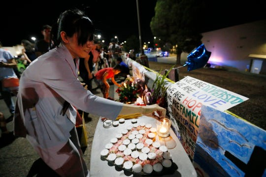 Jessica Lam set up a table of candles in the shape of a heart at the vigil outside Walmart Tuesday, Aug. 6, in El Paso.