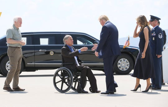 President Donald Trump and first lady Melania Trump greet Texas Gov. Greg Abbott after arriving Wednesday, Aug. 7, 2019, at the El Paso International Airport. U.S. Sen. John Cornyn is at left.