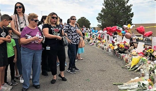 Isabel Barron, center, in black, who works at the Yarbrough Drive Walmart in East El Paso, on Aug.  6, 2019, visits the makeshift memorial behind the Walmart near Cielo Vista Mall. A gunman killed 22 people there Aug. 3, 2019.