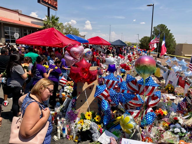 Mourners visit a makeshift memorial on Wednesday, Aug. 7, 2019, near a Walmart in El Paso where 22 were killed and dozens more injured.