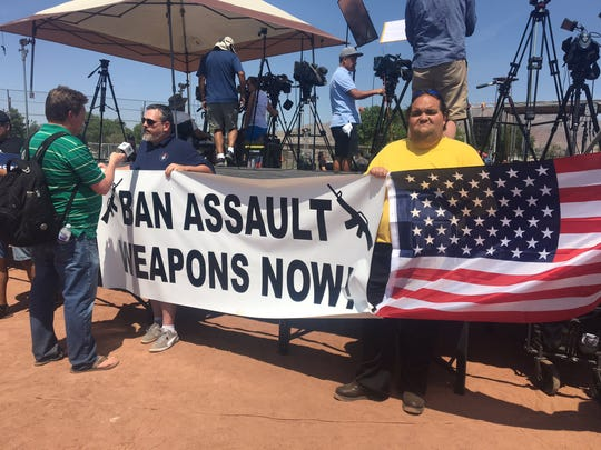 Protesters share their views on assault weapons before a rally gets under way at Washington Park in El Paso on Wednesday, Aug. 7, 2019. The rally is being held in opposition to President Donald Trump's visit to El Paso following the mass shooting at a Walmart.