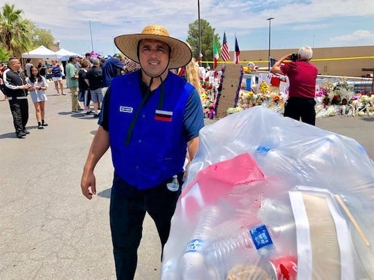 Julio Carrasco, who says he works at the El Paso Mesa Street Walmart store, collects trash left by people visiting a makeshift memorial Aug. 6 behind the Cielo Vista Walmart store where a deadly mass shooting occurred Aug. 3.