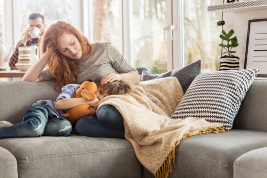 Mother taking care of sleepy child while sitting on couch in the living room