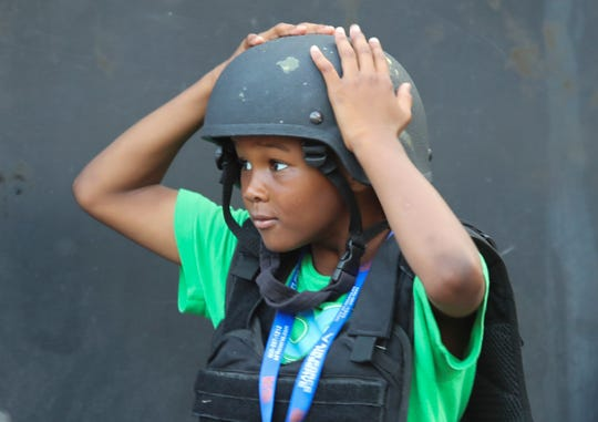 Elijah Drummond, 7, of Wilmington, tries on police tactical defensive gear during the National Night Out events on Wilmington's Rodney Square Tuesday.