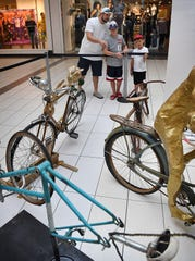 Dustin Calhoun and his sons, Kyler Calhoun, 6, and Bradley Cook, 12, check out the display of Art Bike sculptures at Sikes Senter Mall Wednesday.