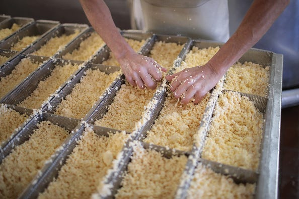 A worker puts Brick cheese curds into forms to make at the Widmer's Cheese Cellars on June 27, 2016 in Theresa, Wisconsin.