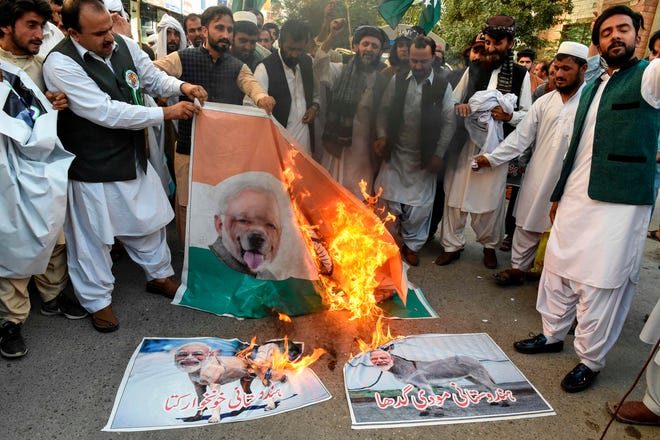 Protesters burn posters featuring images of Indian Prime Minister Narendra Modi during a protest in Quetta on August 6, 2019, a day after India stripped the disputed Kashmir region of its special autonomy.