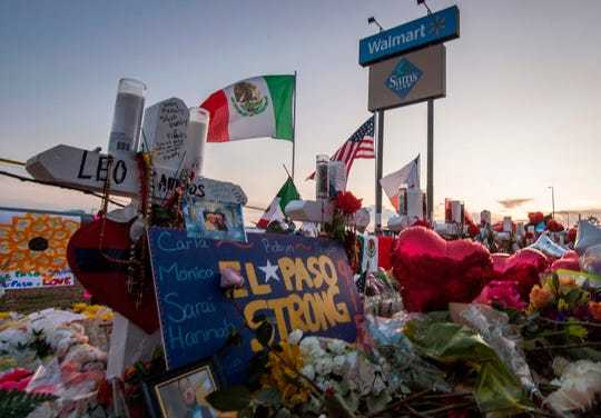 People  pay their respects at the makeshift memorial for victims of the shooting that left a total of 22 people dead at the Cielo Vista Mall WalMart (background) in El Paso, Texas.
