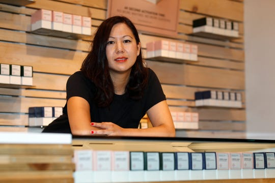 """In this Friday, July 26, 2019 photo, Leslie Siu poses for a portrait next to her cannabis products geared toward women on display in Groundswell dispensary in east Denver. Pregnancy started out rough for her. Morning sickness and migraines had her reeling and barely able to function at a demanding New York marketing job, so like rising numbers of U.S. mothers-to-be, she turned to marijuana. """"l was finally able to get out from under my work desk,"""" said Siu, who later started her own pot company and says her daughter, now 4, is thriving."""