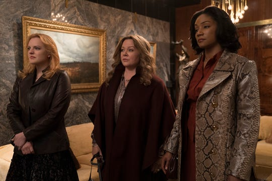 "Elisabeth Moss (far left), Melissa McCarthy and Tiffany Haddish play mob wives who make the most of their turn at gangland success in ""The Kitchen."""