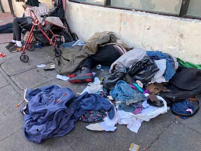 In this July 25, 2019, file photo, sleeping people, discarded clothes and used needles are seen on a street in the Tenderloin neighborhood in San Francisco.