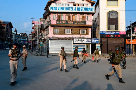 """In this photo taken on August 5, 2019, Indian paramilitary troopers patrol during a curfew in Srinagar. - India's home affairs minister on August 6 hailed """"historic"""" legislation to bring Kashmir under its direct control, as New Delhi stepped up its clampdown on dissent in the restive Muslim-majority region."""
