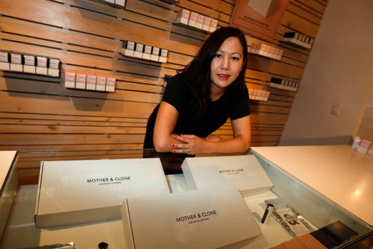 In this Friday, July 26, 2019 photo, Leslie Siu poses for a portrait next to her cannabis spray products geared toward women on display in Groundswell dispensary in east Denver.