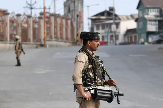 """Security personnel stand guard on a street during a curfew in downtown Srinagar on August 6, 2019. - India's home affairs minister on August 6 hailed """"historic"""" legislation to bring Kashmir under its direct control, as New Delhi stepped up its clampdown on dissent in the restive Muslim-majority region."""