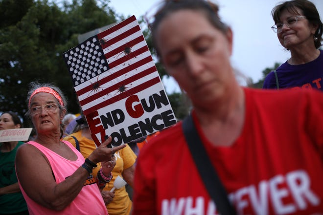 Advocates of gun reform legislation hold a candle light vigil for victims of recent mass shootings outside the headquarters of the National Rifle Association August 5, 2019 in Fairfax, Virginia. Thirty-one people have died following the two mass shootings over the weekend in El Paso, Texas and Dayton, Ohio.