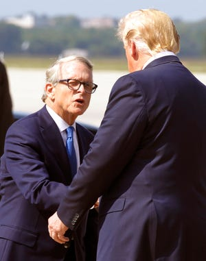 Ohio Governor Mike Dewine is greeted by President Donald Trump at Wright-Patterson Air Force Base,.