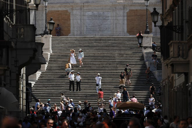 People walk down the Spanish Steps, in Rome on Aug. 7, 2019. Police started the enforcement of a law designed to protect monuments and landmarks and are forbidding people from sitting on the Spanish steps since they are considered a monument.