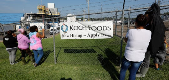 Friends, coworkers and family watch as U.S. immigration officials raid several Mississippi food processing plants, including this Koch Foods Inc., plant in Morton, Miss.