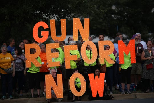 Advocates of gun reform legislation hold a candle light vigil for victims of recent mass shootings outside the headquarters of the National Rifle Association on Aug. 5, 2019, in Fairfax, Va. Thirty-one people have died following the two mass shootings over the weekend in El Paso, Texas, and Dayton, Ohio.