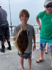Brady Evans, 11 of Montoursville, Pennsylvania, holds a keeper fluke he landed on the Jamaica II party boat.