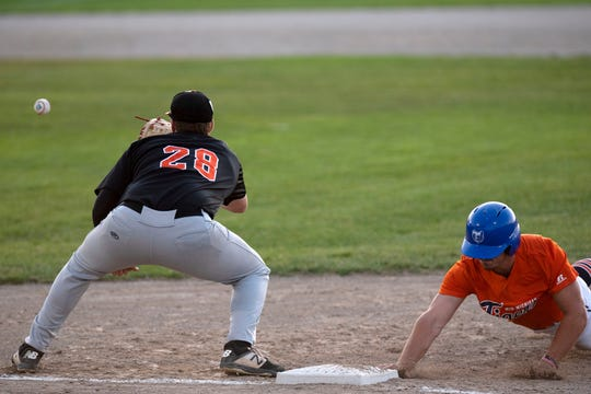 Mid Michigan Tigers' Brendan Gausselin (22) slides back to first base as Lombard Orioles' John Carmondy (28) catches the ball during the opening game of the NABF World Series on Wednesday, Aug. 7, 2019 at C.O. Brown Stadium in Battle Creek, Mich. The Orioles defeated the Tigers 4-2.