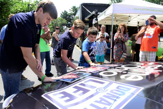 NASCAR Xfinity Series driver Joey Gase, left, leaves his hand print on his race car, along with Nehemiah Miller, 13, of Lakeville and Brendon Ronk, 8, of Crestline. All three had family members who were organ donors.