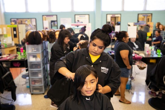 Aaliah Espinosa, 9, has 10 inches of her hair cut off to be donated during her haircut by a Del Mar College summer dual credit cosmetology student as they give free back-to-school haircuts to students in kindergarten through 12th grade on Thursday, Aug. 8, 2019.