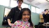 Del Mar College cosmetology students give  free hair cuts to grade school students.