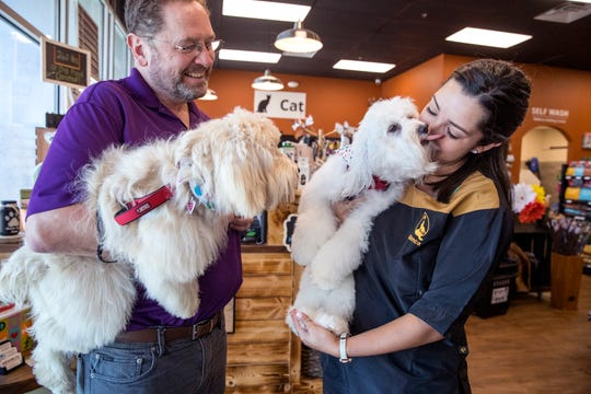 Joseph Eberhard, from left, holds his dog, Jolene, as his other Bichon Frise, Darla, is brought out after being groomed by Earthwise groomer Bianca Chadis on Thursday, August 8, 2019. Earthwise is a new health-conscious pet supply store on the Southside and also features grooming and a self-wash station.