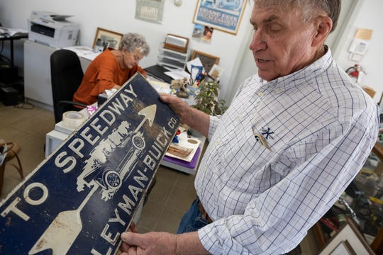 Ralph Crawford shows off an old sign at Rallye Motors in Reading, Ohio, on Thursday. He has owned and run Rally Motors for over 50 years and is selling the business and will be auctioning off cars, road signs and Cincinnati-related memorabilia at 12 p.m. Sunday, Aug. 11, 2019.