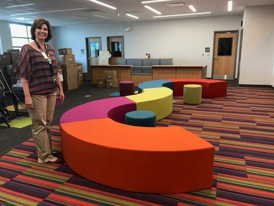 Principal Sheila Taylor shows off more color in the Orchard Hills library.