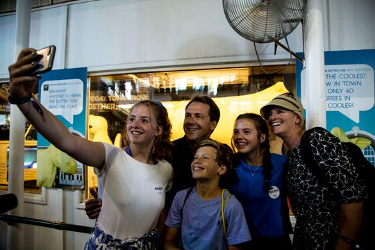 Steve Bullock, Governor of Montana, and his family take a selfie with the butter cow on the first day of the Iowa State Fair on Thursday, Aug. 8, 2019, in Des Moines.