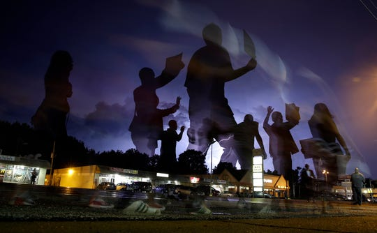 In this Aug. 20, 2014, file photo, protesters march in the street as lightning flashes in the distance in Ferguson, Mo.