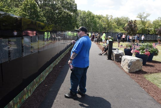 Jeff Brown, 60, of Flat Rock views the Moving Wall Thursday at Livonia's Ford Field. The half-size replica of the Washington, D.C., Vietnam Veterans Memorial has been touring the country for 30-plus years.