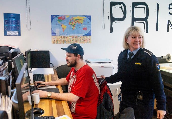 """Inmate Fredrik Soerfjordmo designs artwork on a computer, watched by works manager Janne Hasle, in the digital print shop at Halden Prison in Norway. Staff at Halden are not armed. Instead, they practice """"dynamic security,"""" a disciplinary system based on relationship-building, communication and mutual trust."""
