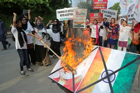 Pakistani students burn a poster of Indian Premier Narendra Modi during an anti-Indian rally in Lahore, Pakistan, Wednesday, Aug. 7, 2019. Pakistan has decided to downgrade its diplomatic ties with neighboring India and suspend bilateral trade in response to New Delhi's decision to reduce the special status of Kashmir, a Himalayan region claimed by both countries.